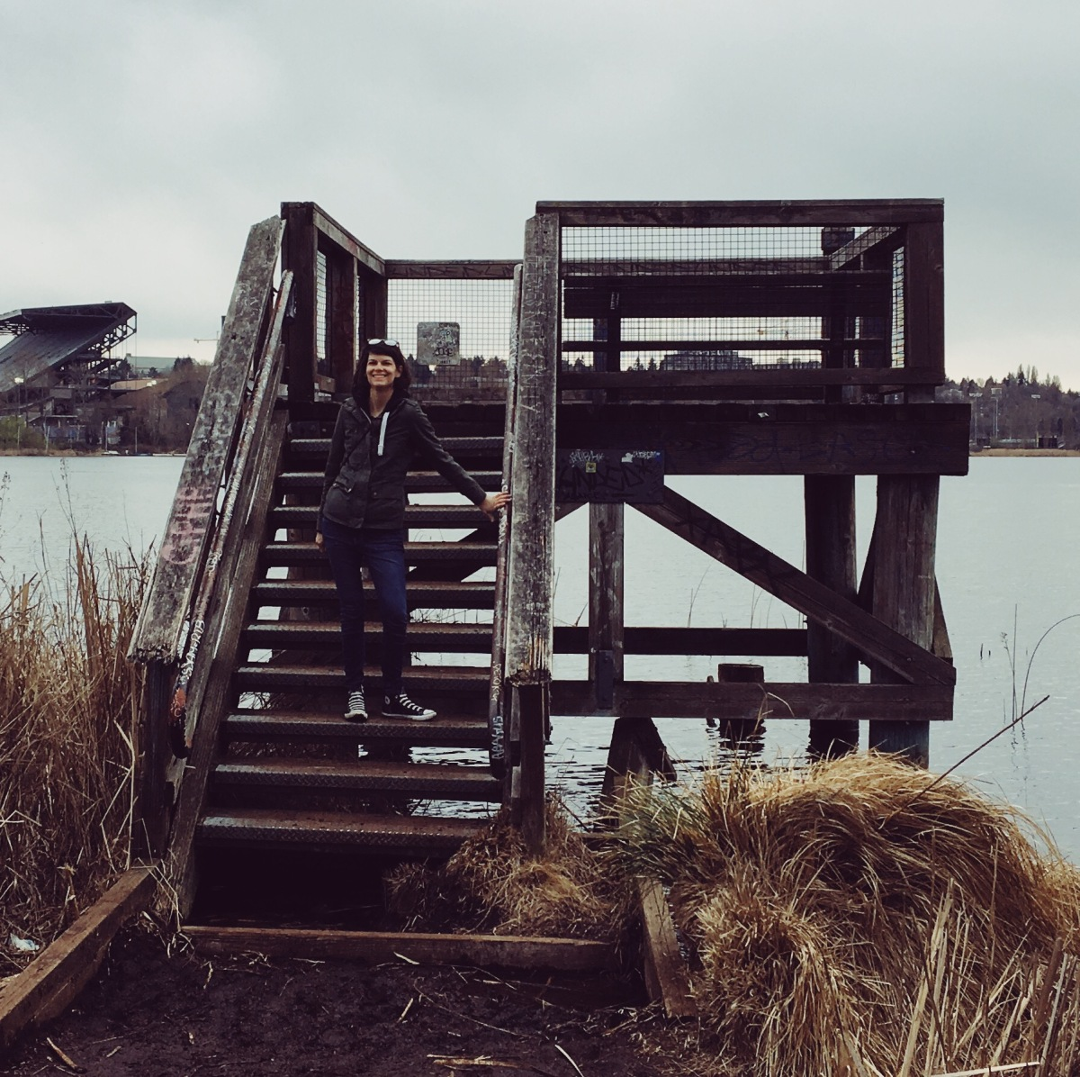 Holly standing on the steps of the raised observation platform overlooking Lake Washington on the Arboretum Waterfront Trail near the Washington Park Arboretum in Seattle, WA
